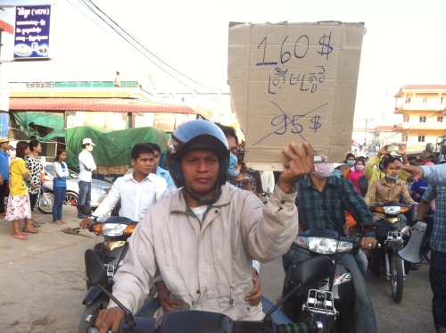 Worker with home-made sign: US$160 not US$95